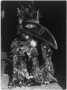 British Columbia, Dancer wearing raven mask with coat of cormorant skins during the numhlin ceremony.