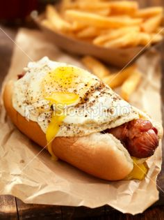 A Bacon Wrapped Hotdog, with a Fried Egg and a Basket of Fries.  Breakfast? Dinner? Something full of hunger in the middle?