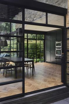 The architects of this extension chose Crittall-style glazing to encase the single-height space. These black gridded frames also encompass a mono-pitched glass roof.