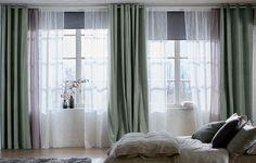 Ett ljust sovrum och spröjsade fönster med svarta mörkläggande rullgardiner, ett lager skira vita gardiner som filtrerar dagsljuset och ett lager tjocka grågröna gardiner för avskildhet.