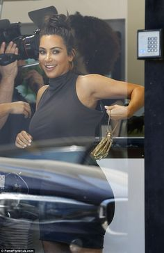 Kim Kardashian squeezes her shapely rear into a turtleneck dress