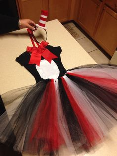 Cat in the Hat costume - black leotard with red bow and white oval patch; black headband with red and white top hat; and black, red and white tutu
