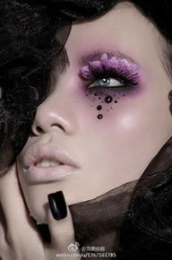 Gems and feather lashes accent purple smokey eye make-up.