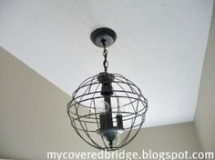 Mycoveredbridge  blog took a ickly brass chandelier, removed peices, added two wire hanging baskets with some spray paint and ended up with this fabulous Ballard knock-off!