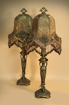 Pair of handsome, painted metal table lamps, each with a tiny fairy at the base. Brown toned pair of 'LOTUS BELL' shaped shades are covered with rich, gold metallic lace, with old, gold iris beaded appliqués in each of the bottom sections of the shades. Hand beaded fringe.