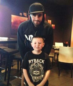 Seth Rollins and a fan. I love the photos of them with kids, it reminds me that they have so much heart to go with all that talent.