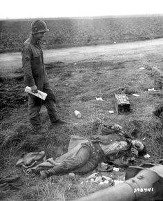U.S. Army Cpl. Army Corporal William R. Kamp examines the corpse of German soldier near the German killed in battle defending the village of Frauwüllesheim from the Allied forces. In the foreground can be seen the muzzle of a German light field howitzer(leichte Feldhaubitze, 10.5cm leFH 18/40), light field howitzer. Frauwüllesheim, North Rhine-Westphalia, Germany. 28 February 1945. Image taken by Jack Kitzerow.