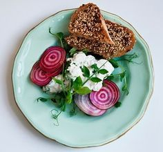 creamed feta with hot sesame toasts and slices of beetroot on a shiny ceramic plate