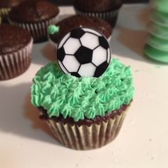From scratch chocolate cupcakes with homemade buttercream icing. Used green food coloring to make the icing 'grass' like. And topped them with soccer ball rings that the kids can keep!  Fun end of season soccer party!