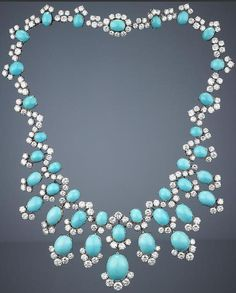 A turquoise and diamond necklace, by Bulgari, 1960s. Of fringe design, the front of the necklace composed of twelve pendants, each set with oval turquoise cabochons, accentuated by brilliant-cut diamond partial surrounds, suspended from a similarly-set undulating neckchain, signed Bulgari.
