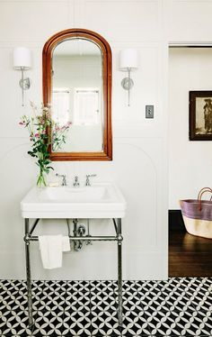 White Bathroom with Graphic Tile Floors and love the arched mirror