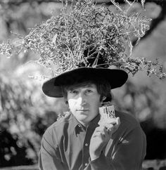"""Beatles singer, songwriter and guitarist John Lennon in the garden at his home at Kenwood, Weybridge, Surrey, 1965. He is holding a porcelain jar and wearing a hat adorned with dead fern fronds. """" (Photo by Robert Whitaker/Getty..."""