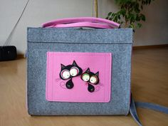 A cute briefcase, gray and pink, with two cats on it, made almost entirely with felt.  You can order it on Etsy.