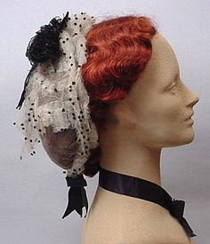 1860s white tulle and black silk ribbon cap. Meant to sit a little further up and forward. From the Mary Quite Contrary costume site, this is probably from an old Ebay listing.