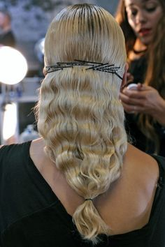 Haute Hairstyles That Rocked The 2013 Runway: At Thakoon, the idea of duality showed up again with the sleek roots and wavy hair combo, but this time it was accompanied by bobby pins functioning as a giant barrette. We love the creative use of pins and are definitely snagging this look for ourselves.