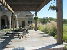 Flagstone patio with cedar pergola backed with native grasses.