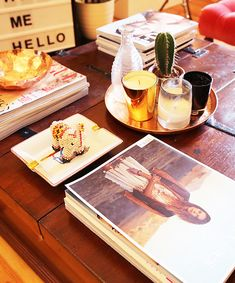 Dark wooden coffee table filled with fashion magazines.