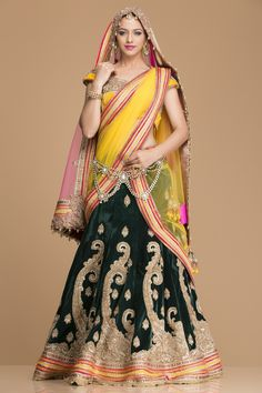 Look no less a mughal era princess in this dark green velvet lehenga heavily embellished zardozi work with a heavy kali and lace golden border. The yellow blouse is again heavily ornated. It comes with set of two net dupattas, one in pink with heavy work border and one in yellow  with heavy  lace border, so that one can be draped while the other can cover your head for the perfect bridal look.