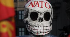 A mask during an anti-NATO protest rally These Five Steps Will End US Foreign Policy of Military Intervention