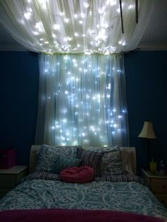 Sparkly lights and curtains above bed