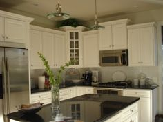 I like the white cabinets with dark countertop.  Also the staggered height of cabinets with trim piece on top.