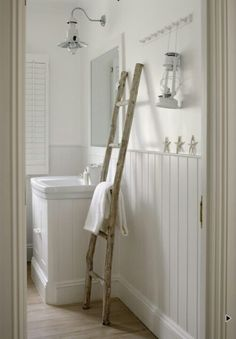 love the driftwood ladder, white cladding, vintage lighting and white linene in this bathroom