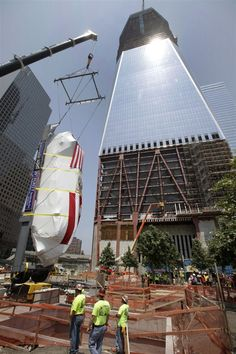 The Fire Department of New York's Ladder Company 3 fire truck is lowered by crane into the National September 11 Memorial Museum, in front of One World Trade, in New York, Wednesday, July 20. This fire truck was used to evacuate people from the World Trade Center towers during the terror attacks on Sept. 11, 2001.