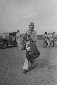US Army nurse carrying her gear prior to boarding a plane for transport after she was liberated from a Japanese internment camp during WWII. Location:Manila, Luzon, Philippine Islands Date taken:February 1945 Photographer:Carl Mydans