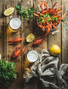 #Wheat beer and boiled crayfish Two pints of wheat beer and boiled crayfish with lemon and parsley over old wooden rustic background top view