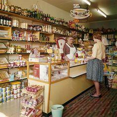 Mevrouw de Koning achter de toonbank van haar levensmiddelenwinkel. Nederland, Boskoop, 1961.  English: Grocery. The Netherlands, Boskoop, 1961.