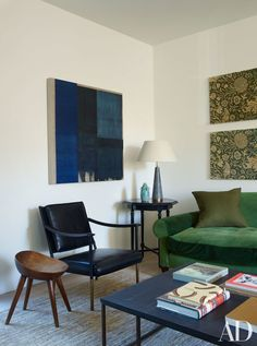 In the living room, an abstract painting is juxtaposed with antique velveteen panels by William Morris.