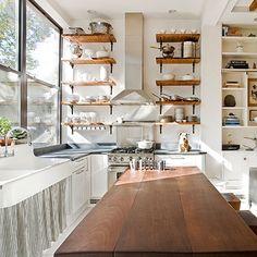 soapstone counter, farmhouse sink, open shelves with dark (wrought iron?) brackets, farm table.