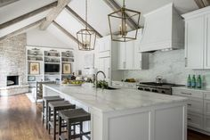 With vaulted ceilings, marble surfaces and crisp white cabinetry, this contemporary kitchen remodeled by Julie Bradshaw seems light and airy. Wood floors and nature-inspired prints add a rustic touch to the space.