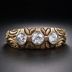 Art Nouveau Diamond Gypsy Ring   A trio of very bright-white and sparkling European-cut diamonds radiate from the top of this deeply carved 'Gypsy' style ring, crafted in 18 karat yellow gold with a graceful leaf and flower motif combined with abstract ornamentation. A marvelous three-stone sparkler, circa 1900 / JV