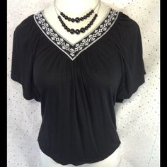 WHBM Embroidered V-neck Top XS This top is gorgeous!  Black knit with white embroidered neck line.  Shirt sleeves are similar to dolman style,  very flattering!  Hand wash and worth it.  Great quality you expect from WHBM. White House Black Market Tops Tunics
