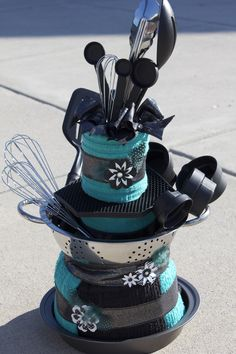 This kitchen towel cake includes (and subject to change on availability of items) 1-9in Round cake pan 6-terry cloth hand towels, 1 large measuring cup, 1 strainer, 4 wash clothes, 3 whisks, 1 ladle, 1 spatula, 1 salad tongue, 1 noodle ladle, 1 set of measuring spoons and cups. and 1 hot pad. @HeatherParkinson  @Tana