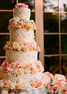 Traditional four-tiered white wedding cake with sugar paste flowers encircling the top of each tier, as well as the top. Quite pretty. by Ana Rosa