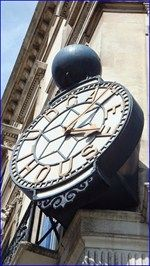 The clock is located on Ludgate House in Fleet Street. Ludgate House was constructed in the nineteenth century as the headquarters of Thomas Cook, who at the time were the worlds leading travel group.