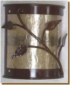 """Silver mica accents the rust finish as shown in this picture. Similar to the basic twig wall scone but with leafs. Wall sconce is made of tree bark iron and accented with the cottonwood leaf. All finishes are available. This light is UL listed to hold up to two 60 watt bulbs. 10"""" Wide 5"""" Deep 12"""" High."""