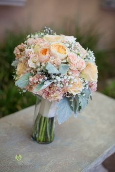 Bridal bouquet with peach peonies, babies breath, pink spray roses, and dusty miller leaves wrapped in white ribbon | Lasting Images Photography | villasiena.cc