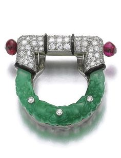 Jadeite, ruby, lacquer and diamond clip, 'Stirrup', Cartier, circa 1925 Composed of carved jadeite highlighted with single-cut diamonds, surmounted with pavé-set circular- and single-cut diamonds, accented with black enamel lines and two ruby beads, signed Cartier, numbered.