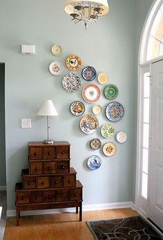 Os pratos na parede fazem as vezes de quadros, enfeitam, de forma singela, o hall de entrada e deixam o ambiente mais delicado