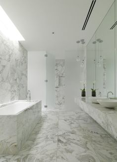 Marble covers the floor, walls, counter, and shower area of this bathroom, keeping it bright, clean, and modern.