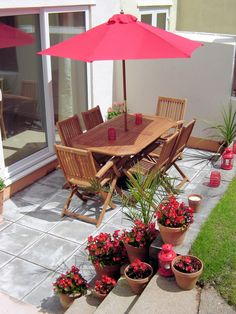 Patio with wooden table & chairs, red garden parasol & terracotta pots filled with red begonias.