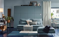 A medium sized livingroom furnished with a turquoise three-seat sofa and a footstool in the same colour. Combined with a white storage table and a large storage combination in grey-turquoise.