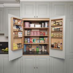 Love the spice cabinet.  The kitchen has many elements adding to its traditional charm, such as Shaker-style peg rails, an integrated larder unit, wall inset spice racks and a limestone floor. A richly toned iroko worktop adds warmth to the scheme, whilst honed Nero Impala granite upstands feature decorative edging and cabinet doors take on a classic style painted in Farrow & Ball's pale powder green. Designed and made by Tim Wood