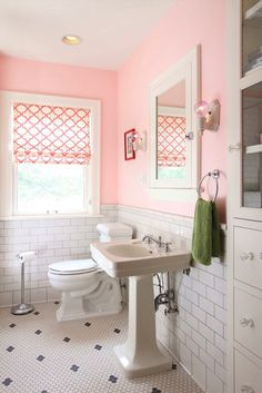 Adorable pink girl's bathroom with pink paint color paired with subway tile with dark ...