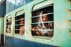 Faded elegance: Trains carry some seven billion passengers across India every year and this image, taken in Jodhpur, captures a young woman on her daily commute