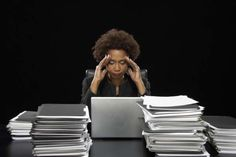 Businesswoman using laptop surrounded by files, with hands to head.: Many employees are not taking time off, causing stress, anxiety and other negative effects.