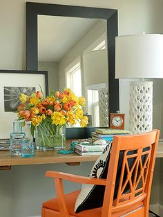 Love the bright pops of color - a former office desk makes a roomy bedside table. An old wooden chair painted bright orange adds color and modern flair.